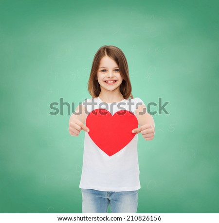 childhood, cahrity, education, love and people concept - smiling little girl sitting with red heart cutout over green blackboard background - stock photo