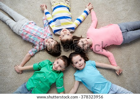 childhood, fashion, friendship and people concept - group of happy smiling little children lying on floor and holding hands - stock photo