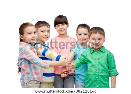 childhood, fashion, friendship and people concept - happy little children with hands on top - stock photo