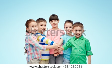 childhood, fashion, friendship and people concept - happy little children with hands on top over blue background - stock photo