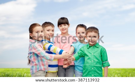 childhood, fashion, friendship and people concept - happy little children with hands on top over blue sky and grass background - stock photo