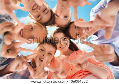 childhood, fashion, friendship and people concept - happy smiling children showing peace hand sign and standing in circle over blue sky and clouds background - stock photo