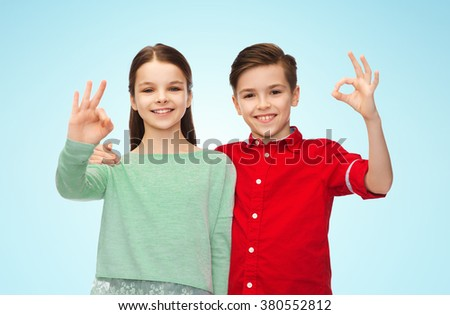 childhood, fashion, gesture and people concept - happy smiling boy and girl hugging and showing ok hand sign over blue background - stock photo