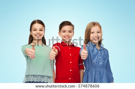childhood, fashion, gesture and people concept - happy smiling boy and girls showing thumbs up over blue background - stock photo