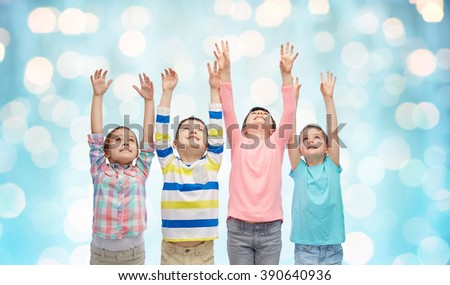 childhood, fashion, gesture and people concept - happy smiling children raising fists and celebrating victory over blue holidays lights background - stock photo