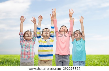 childhood, fashion, gesture and people concept - happy smiling children raising hands and celebrating victory over blue sky and grass background - stock photo