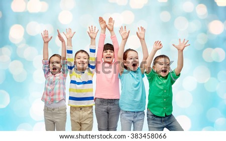 childhood, fashion, gesture and people concept - happy smiling friends raising fists and celebrating victory over blue holidays lights background - stock photo