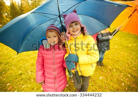 childhood, friendship, season, weather and people concept - group of happy kids with umbrella in autumn park - stock photo