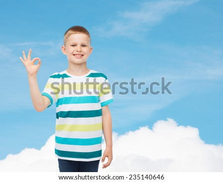 childhood, gesture and people concept - smiling little boy in casual clothes making ok gesture over blue sky background - stock photo
