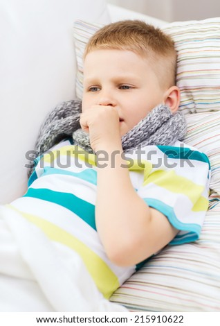 childhood, healthcare and medicine concept - ill boy with flu coughing at home - stock photo