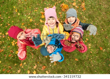 childhood, leisure, friendship and people concept - group of happy children waving hands in autumn park from top - stock photo