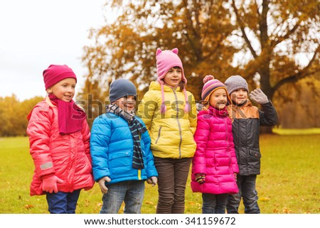 childhood, leisure, friendship and people concept - group of happy kids in autumn park - stock photo