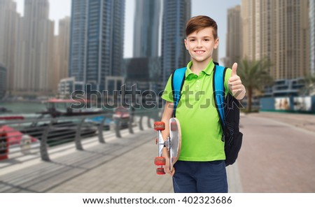 childhood, leisure, gesture, school and people concept - happy smiling student boy with backpack and skateboard showing thumbs up over dubai city street background - stock photo