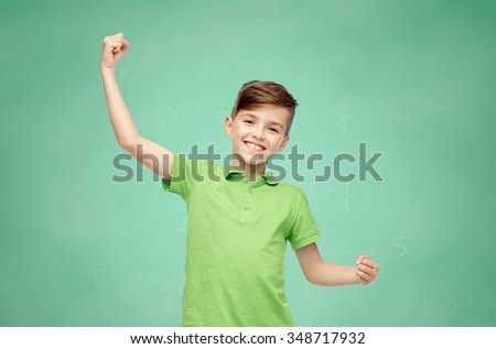 childhood, power, strength and people concept - happy smiling boy in green polo t-shirt showing strong fists over green school chalk board background - stock photo