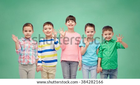 childhood, preschool education, friendship and people concept - group of happy smiling little children holding hands over green school chalk board background - stock photo