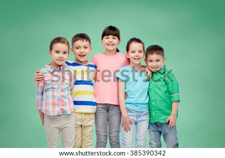 childhood, preschool education, friendship and people concept - group of happy smiling little children hugging over green school chalk board background - stock photo