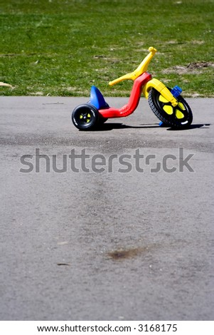 Childhood red and yellow plastic tricycle big front wheel - stock photo