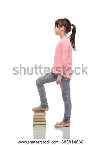 childhood, school, education and people concept - happy little girl stepping on book pile - stock photo