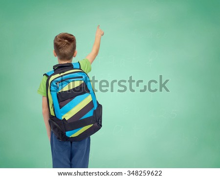 childhood, school, education and people concept - happy smiling student boy with school bag over green school chalk board background - stock photo