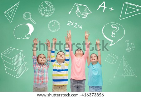 childhood, school, education, gesture and people concept - happy smiling children raising hands and celebrating victory over doodles on green chalk board background - stock photo