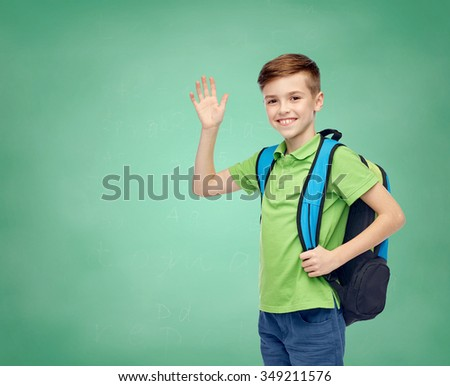 childhood, school, education, greeting gesture and people concept - happy smiling student boy with school bag waving hand over green school chalk board background - stock photo