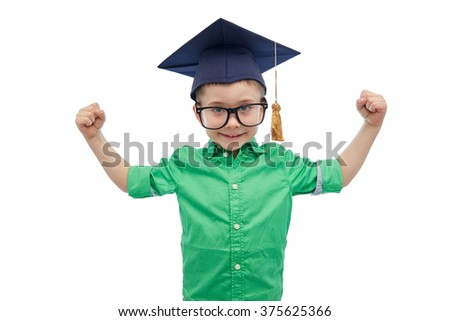 childhood, school, education, knowledge and people concept - happy boy in bachelor hat or mortarboard and eyeglasses showing strong hands - stock photo