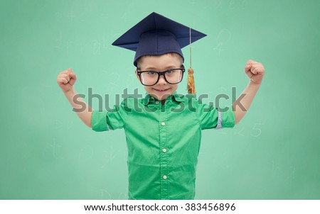 childhood, school, education, knowledge and people concept - happy boy in bachelor hat or mortarboard and eyeglasses showing strong hands over green school chalk board background - stock photo