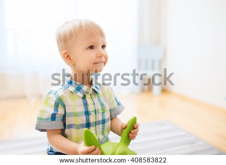 childhood, toys and people concept - happy little baby boy playing with ride-on toy horse at home