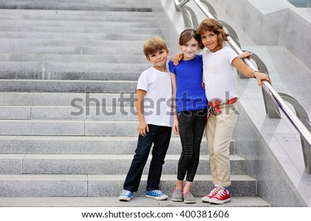 childhood, travel, tourism, friendship and people concept - happy smiling boy and girls hugging over  city street background - stock photo