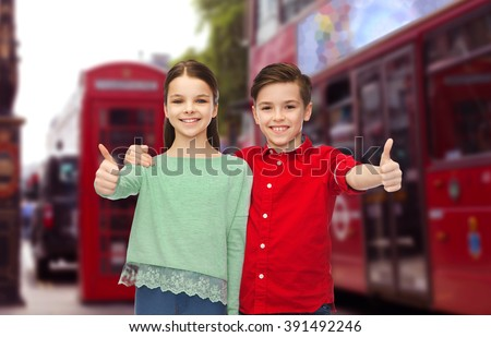 childhood, travel, tourism, gesture and people concept - happy smiling boy and girl hugging and showing thumbs up over london city street background - stock photo