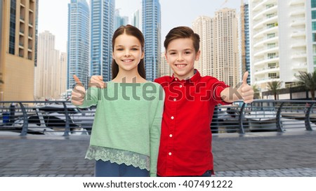 childhood, travel, tourism, gesture and people concept - happy smiling boy and girl hugging and showing thumbs up over dubai city street background - stock photo