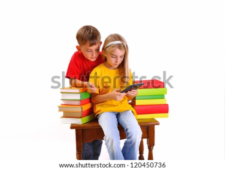Children - a boy and girl reading e-book surrounded by several books isolate on white background - stock photo