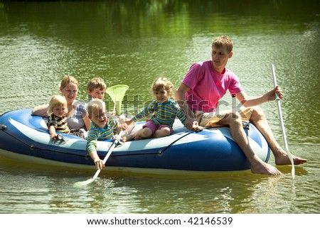 Children and adults float on an inflatable boat and fish a net. - stock photo
