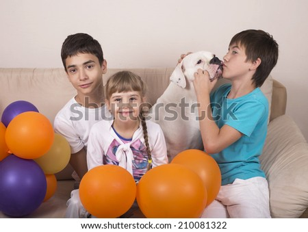 children and dog of breed the American bulldog sit on a sofa in the room
