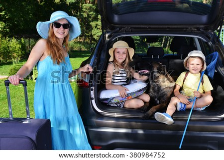 children and dog sits in car - stock photo