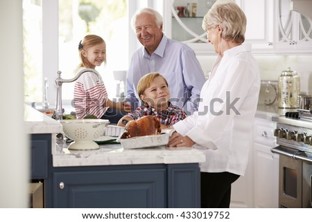 Children And Grandparents Make Roast Turkey Meal In Kitchen - stock photo