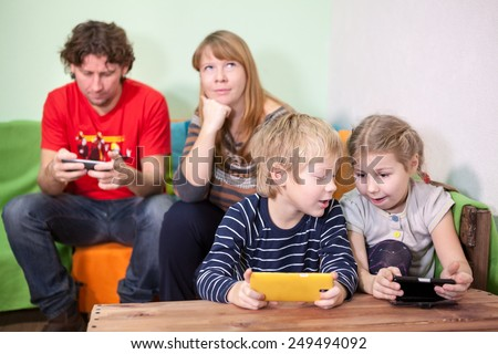 Children and husband are passionate about games in the phones, the mother boring - stock photo