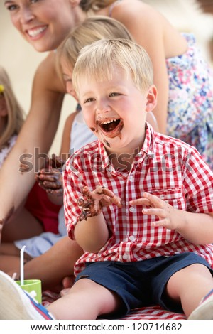 Children And Mother Eating Cake At Outdoor Tea Party - stock photo
