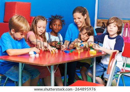 Children and nursery teacher playing with building blocks in a kindergarten - stock photo
