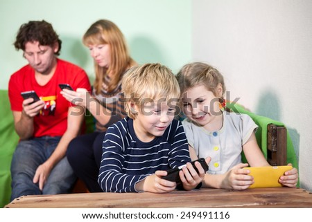 Children and parents playing games on smartphones - stock photo
