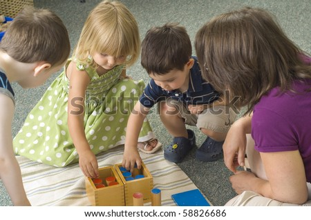 Children and teacher learn while playing with different shapes at the preschool class. - stock photo
