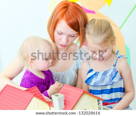 Children and their mother playing with dollhouse - stock photo