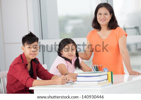 Children and their mum smiling and looking at camera inside - stock photo