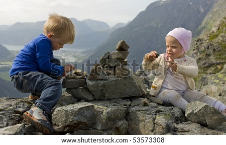 Children (1 and 3 years old) building a cairn on a mountaintop. Rauma, Molde - stock photo