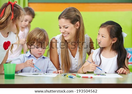 Children are creative painting in kindergarten with a happy nursery teacher - stock photo