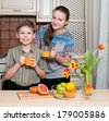 Children are drinking quizzed orange juice from glasses in the kitchen. Healthy drinks. - stock photo