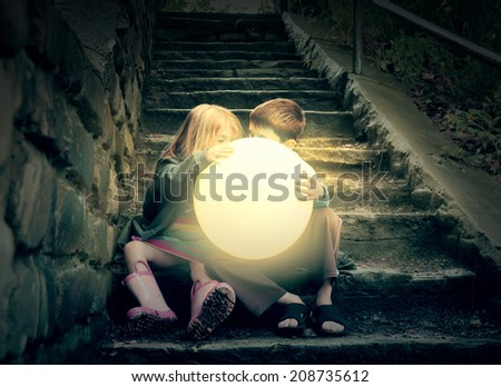 Children are holding the bright yellow glowing sun on wet dark stairs for a weather or season concept about the environment. - stock photo