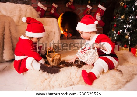Children are sitting near fireplace and play with cones - Christmas decorations - stock photo