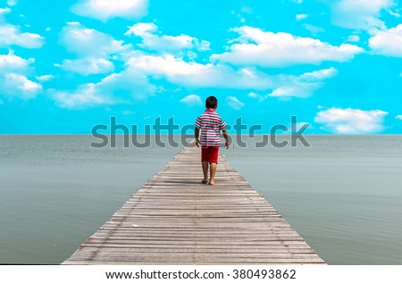 Children are walking on the pier and looking into the distance of the ocean