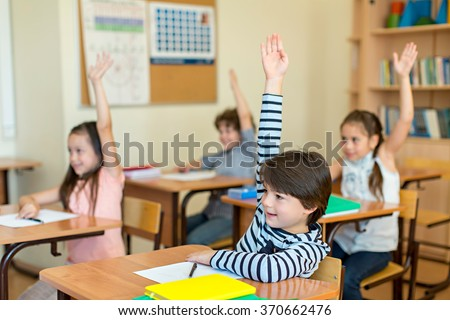 Children at a desk in classroom - stock photo